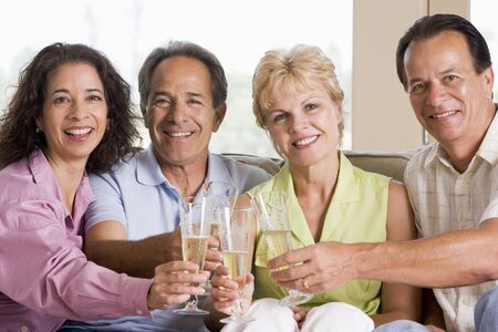 Two couples in living room drinking champagne and smiling photo