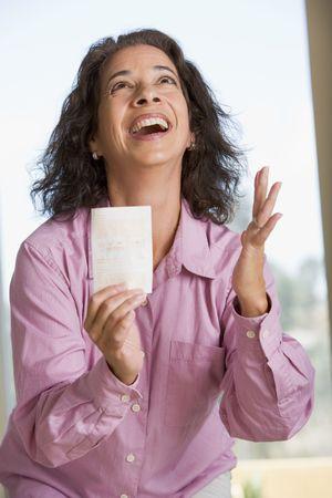 lottery: Vrouw met winnende loterij ticket verheugd en die lacht Stockfoto