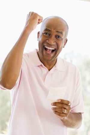 loteria: Hombre con billete de loter�a ganador emocionado y sonriente