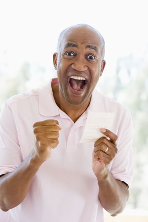 lotteries: Man with winning lottery ticket excited and smiling