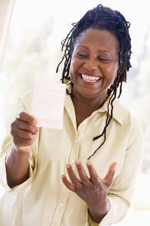 loteria: Mujer con billete de loter�a ganador emocionado y sonriente
