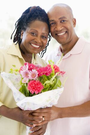 Husband and wife holding flowers smiling photo
