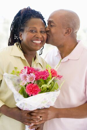 Husband and wife holding flowers kissing and smiling Stock Photo - 3488106