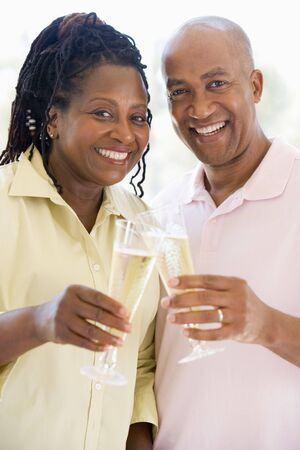 Couple toasting champagne and smiling photo