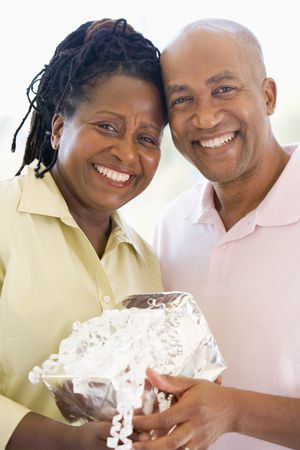Husband and wife holding gift smiling Stock Photo - 3487186