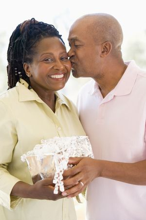 Husband and wife holding gift kissing and smiling photo