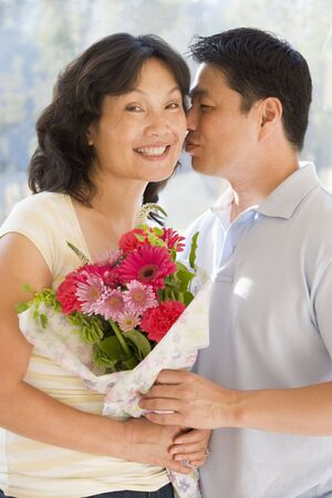 Husband and wife holding flowers kissing and smiling Stock Photo - 3488155