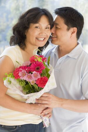 Husband and wife holding flowers smiling Stock Photo - 3487931