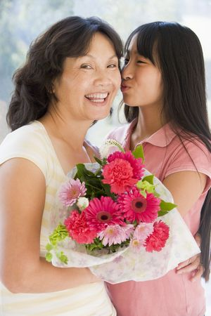 grandmother grandchild: Granddaughter kissing grandmother on cheek holding flowers and smiling