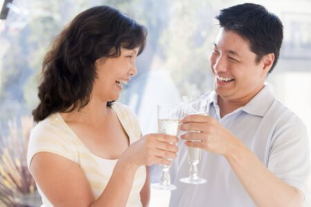 Couple toasting champagne and smiling Stock Photo - 3487000
