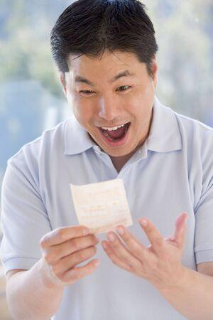 buena suerte: Hombre ganadores de la loter�a con boleto emocionado y sonriente
