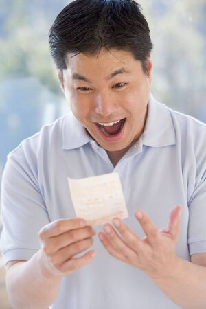 lucky man: Man with winning lottery ticket excited and smiling