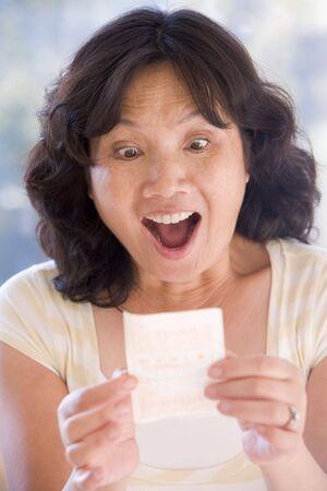 lottery: Vrouw met winnende lot opgewonden en lachend