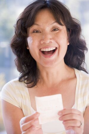 Woman with winning lottery ticket excited and smiling photo