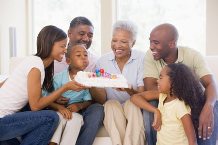 Family in living room smiling with young boy blowing out candles on cake photo