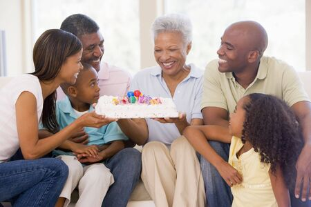 Family in living room with cake smiling photo