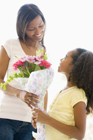 african american mother and daughter: Mother giving daughter flowers and smiling