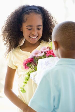 Young boy giving young girl flowers and smiling Stock Photo - 3487023