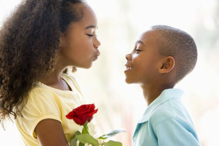Young boy giving young girl rose and smiling Stock Photo - 3486935