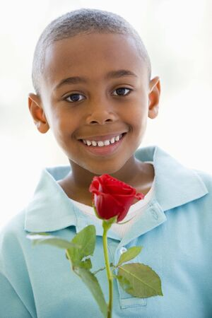 Young boy holding rose smiling Stock Photo - 3487474