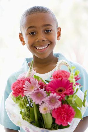 flores de cumplea�os: Chico joven sonriente la celebraci�n de flores  Foto de archivo