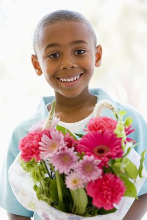 giving gift: Young boy holding flowers smiling Stock Photo