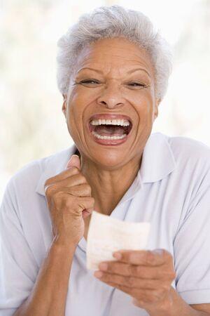 loteria: Mujer con el billete ganador de loter�a emocionada y sonriente