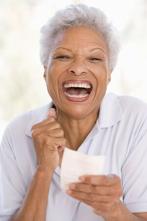Woman with winning lottery ticket excited and smiling Stock Photo - 3485985