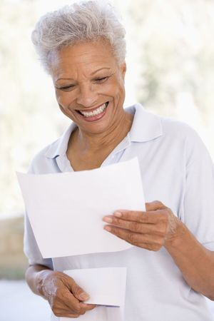woman reading: Woman reading letter smiling Stock Photo