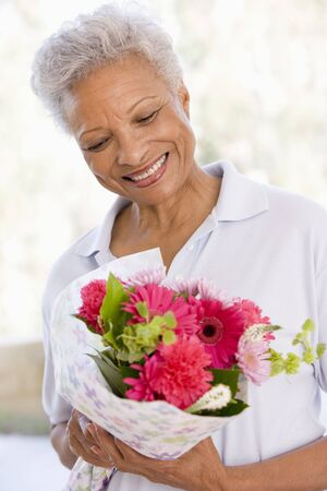 admiring: Woman holding flowers and smiling Stock Photo