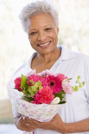bouquet fleur: Femme portant des fleurs et le sourire Banque d'images
