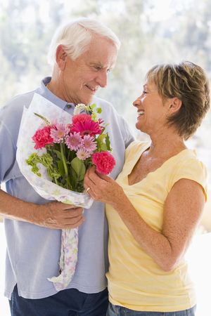 Husband giving wife flowers and smiling Stock Photo - 3488102
