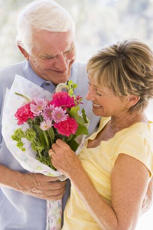 Husband giving wife flowers and smiling Stock Photo - 3487440