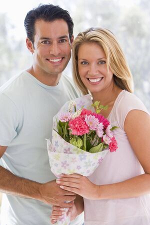 Husband and wife holding flowers and smiling photo