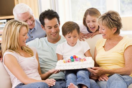 alan: Family in living room smiling with young boy blowing out candles on cake