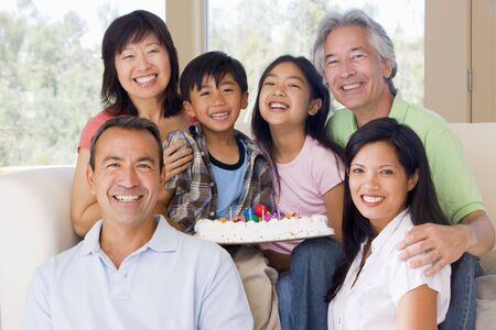 mixed family: Family in living room with cake smiling