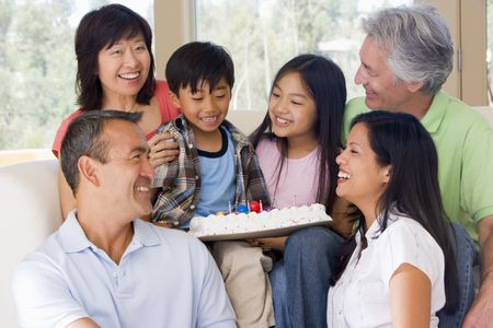 mixed race family: Family in living room with cake smiling