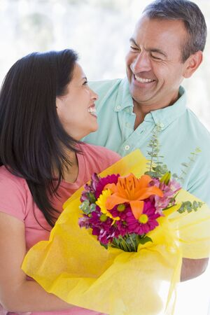 filipino people: Husband and wife holding flowers and smiling Stock Photo