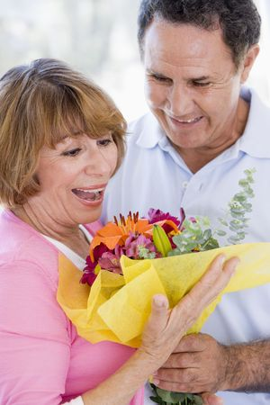 Husband and wife holding flowers and smiling Stock Photo - 3488129