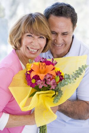 Husband and wife holding flowers and smiling Stock Photo - 3488023