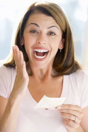 lotto: Woman with winning lottery ticket excited and smiling