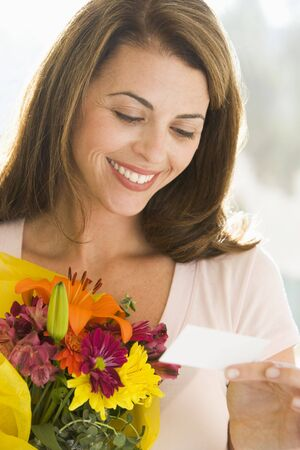 Woman holding flowers and reading note smiling photo