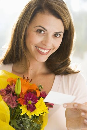 Woman holding flowers and note smiling photo