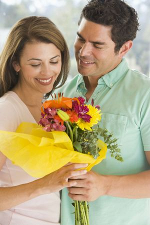 Husband giving wife flowers and smiling Stock Photo - 3488153