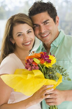 Husband and wife holding flowers and smiling Stock Photo - 3488033