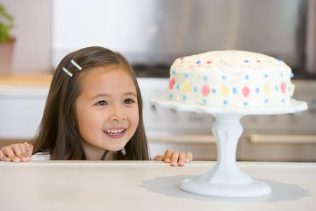 childrens birthday party: Young girl at kitchen counter looking at cake smiling