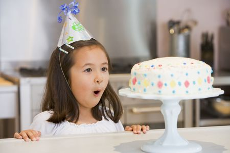 childs birthday party: Young girl wearing party hat at kitchen counter looking at cake smiling