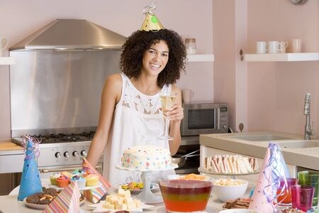 Woman at party holding drink standing by food table smiling Stock Photo - 3487078