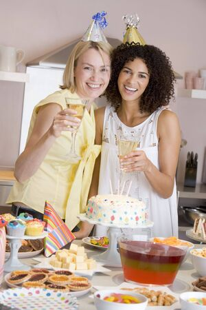 Two women at party holding drinks standing by food table smiling photo