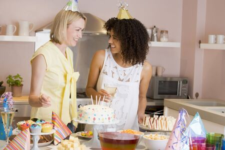 Two women at party standing by food table smiling Stock Photo - 3487223